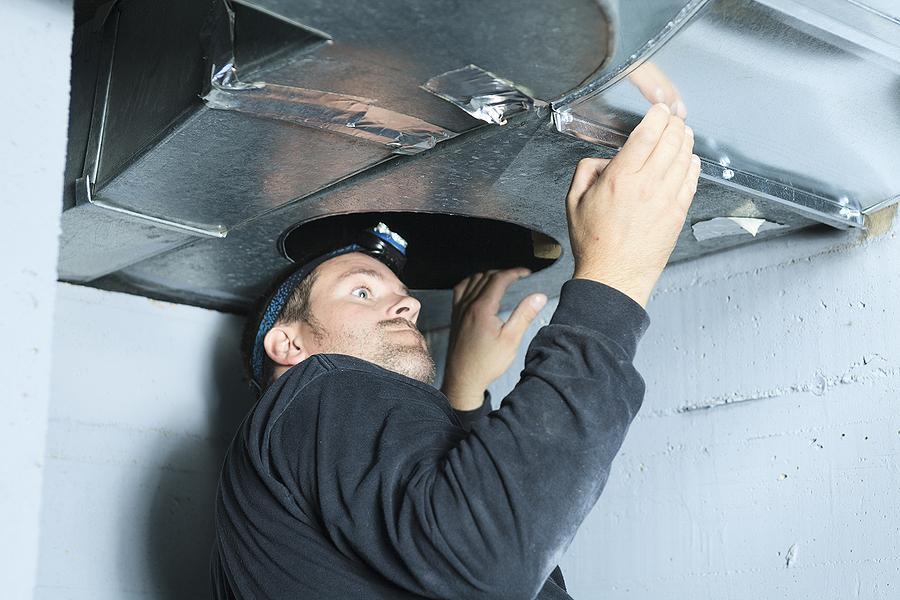 man repairing the air duct
